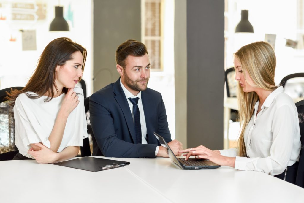 Blonde businesswoman explaining with laptop to smiling young cou