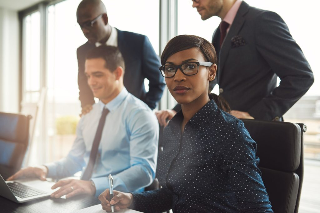 Businesswoman with male co-workers in office