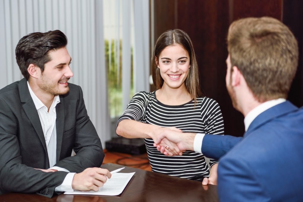 Smiling young couple shaking hands with an insurance agent